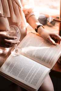 person holding wine glass while reading book